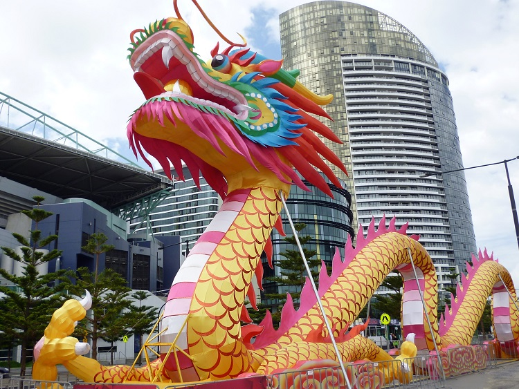 Brightly colored Chinese dragon in front of city buildings to celebrate Chinese New Year.