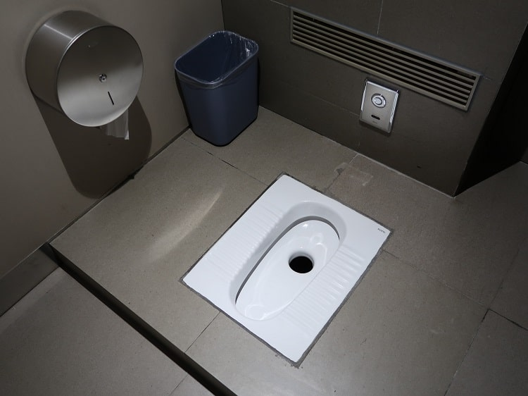 Clean squat toilet in China