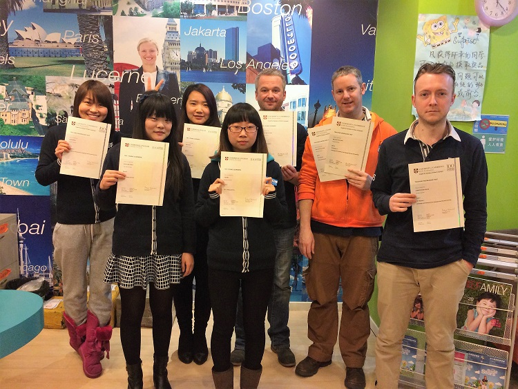 A group of English teachers holding up certificates in a private language institute in China.