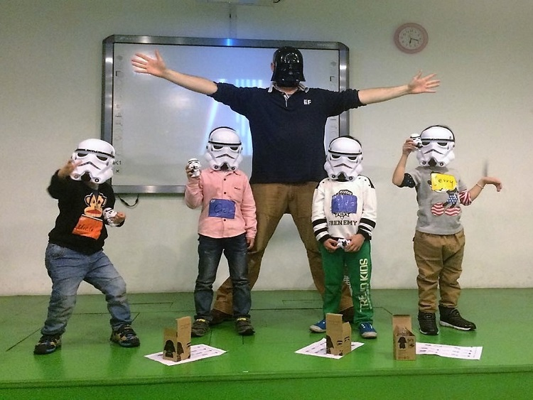 Northern Irishman Malachy Scullion with four kids in a classroom in China wearing Star Wars masks.