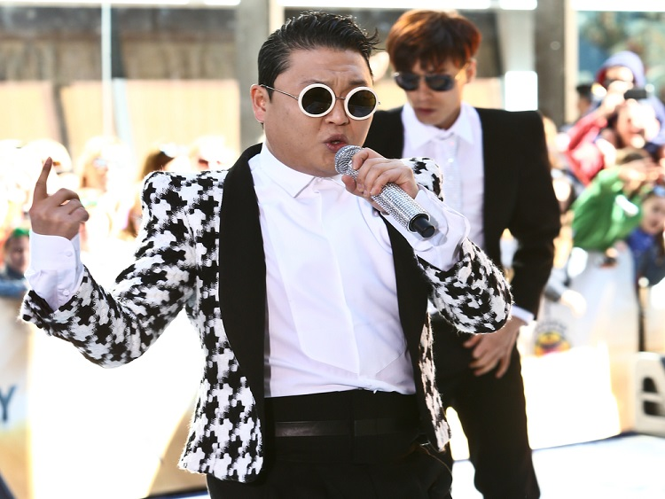 Korean singer Psy singing into a microphone.