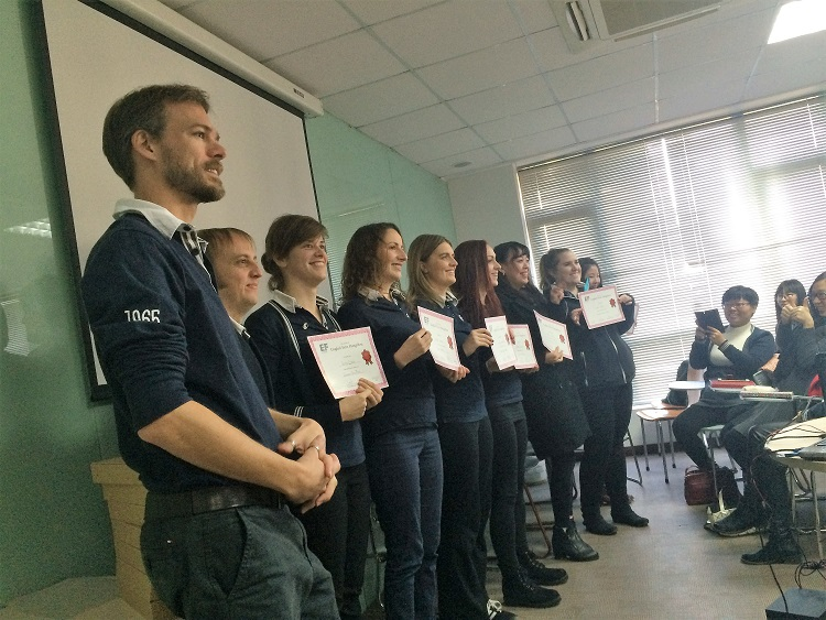 A group of English teachers in China holding up certificates.