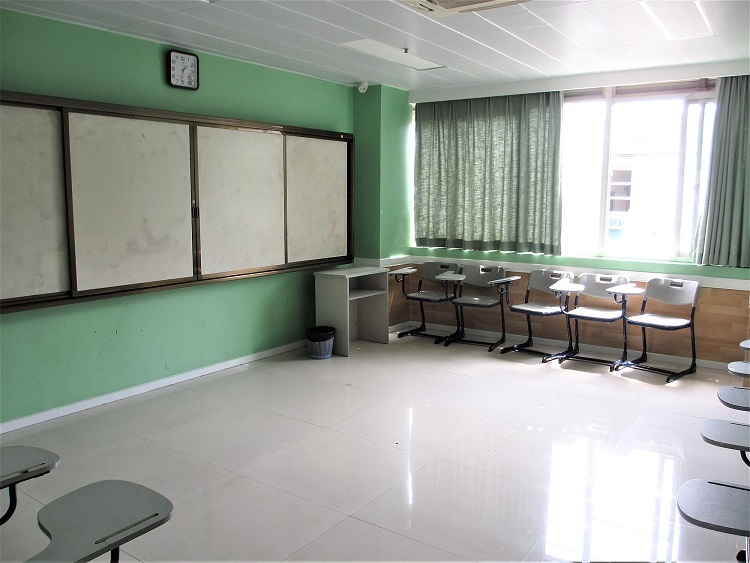 A more modern classroom layout in China with digital board and sliding whiteboard.