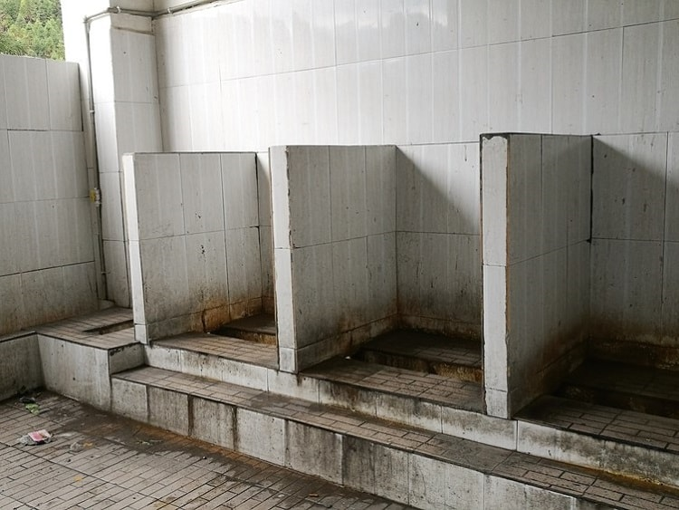An old public toilet without privacy in China.
