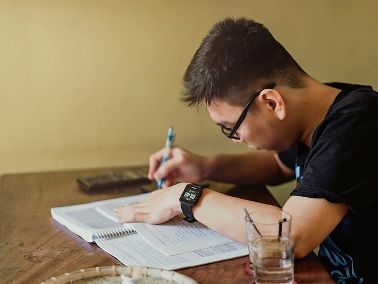 Male Chinese student sitting an exam.