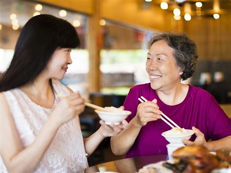 Young Chinese lady eating rice with older Chinese lady.