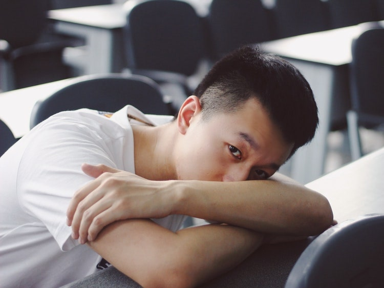 Bored Chinese student laying on desk
