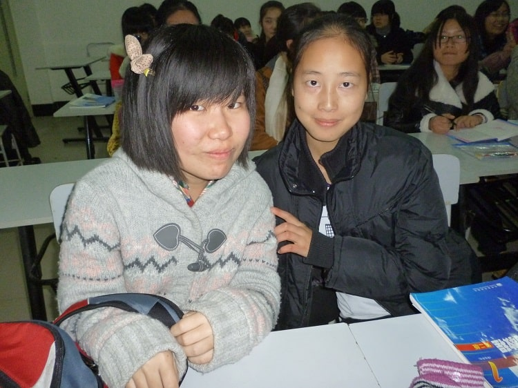 Two female Chinese students sitting together in classroom
