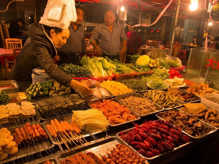 Woman selling fresh food at a market in China